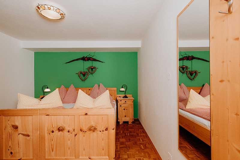 Zimmer mit Bett und Spiegel.